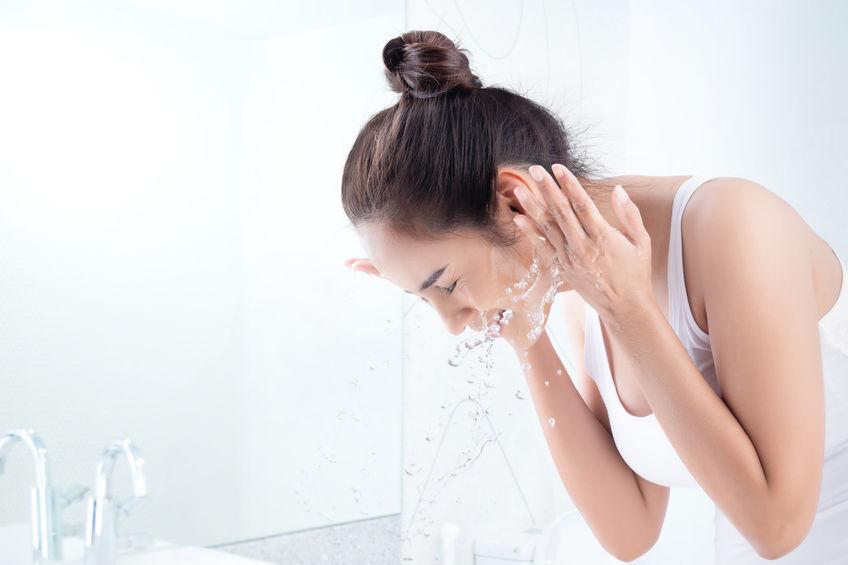 Beautiful woman washing face in the bathroom.