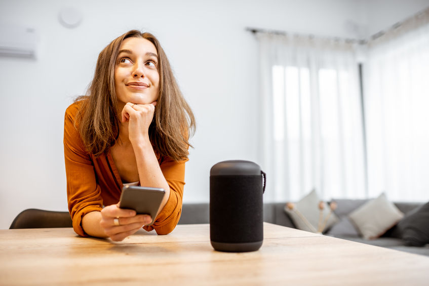 Portrait of a young and cheerful woman with a smart wireless column and phone at home. Concept of smart home and voice command control.