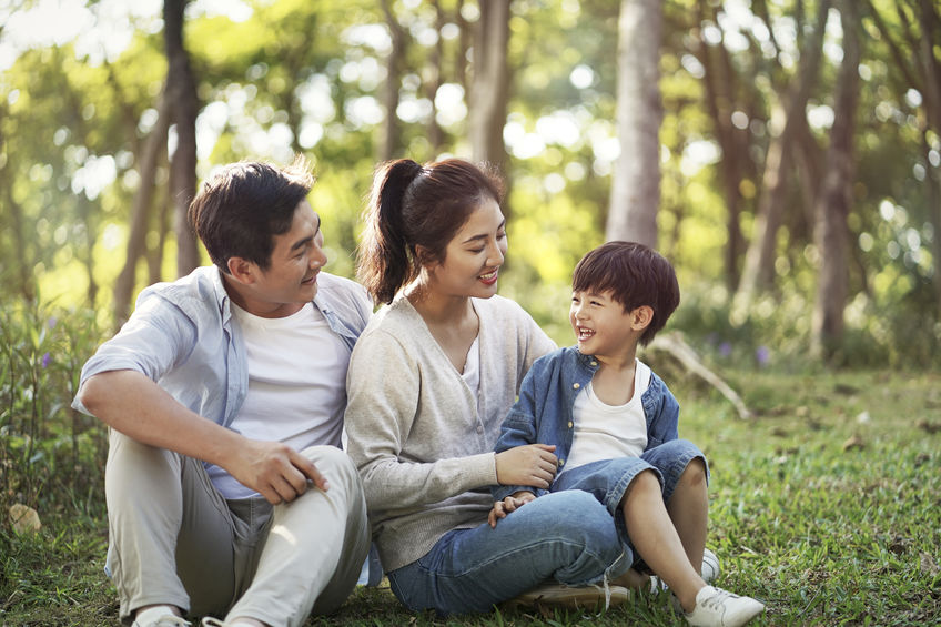 young parents and son having fun outdoors in park.