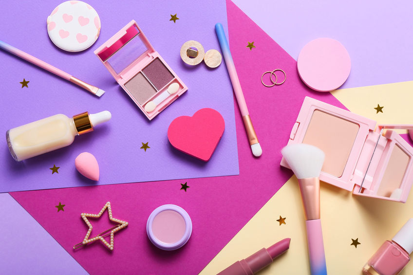 Set of professional decorative cosmetics, makeup tools and accessory on colorful purple background. Beauty, fashion and shopping concept. Flat lay composition, top view.